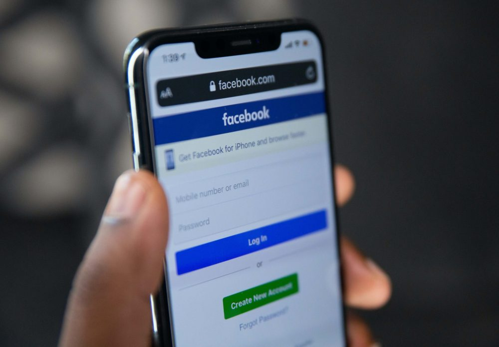 African American hand holding iphone on Facebook's login page.